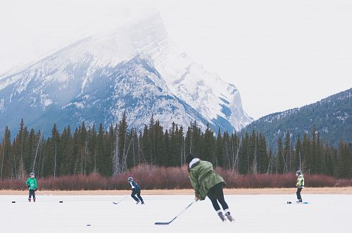 photo people playing hockey on icefield at datyime free for commercial use images