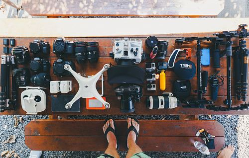 photo person standing near black and white quadcopter drone near cameras on brown wooden table free for commercial use images