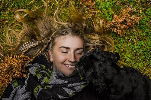 photo smiling woman lying on ground beside black dog at daytime free for commercial use images