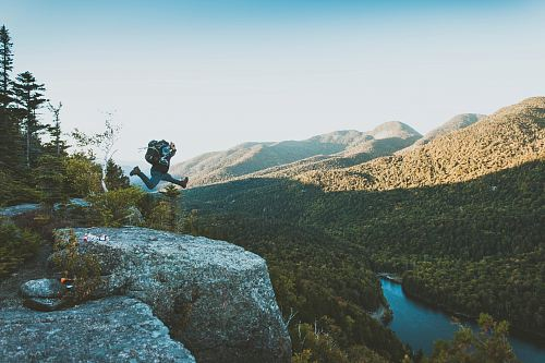 photo time lapse photo of person jumping from cliff within mountain range free for commercial use images