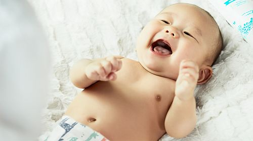 photo topless baby lying on bed smiling free for commercial use images