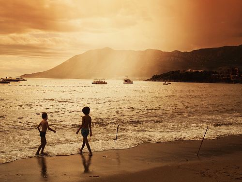 photo two children walking on beach during sunset free for commercial use images