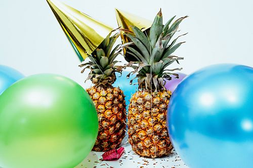 two pineapples with gold party hats near colorful balloons