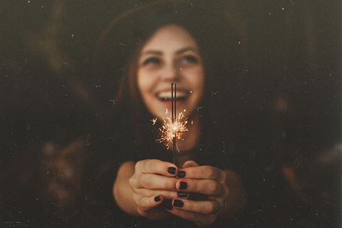 photo woman holding sparklers while smiling free for commercial use images