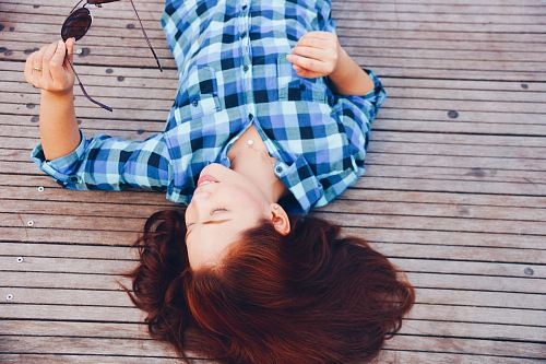 photo woman in blue flannel shirt laying on floor free for commercial use images