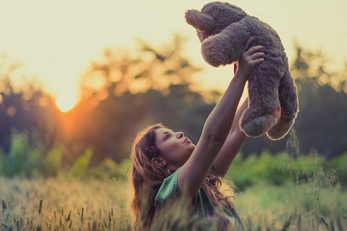 photo woman lifting brown bear plush toy free for commercial use images