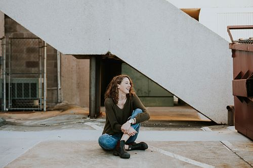 woman sitting near concrete staircase