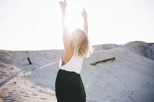 photo woman standing on the desert while her hands up free for commercial use images