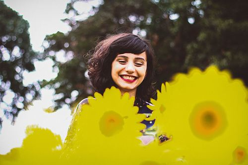 photo woman standing on yellow flowers free for commercial use images