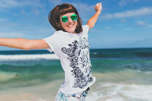 photo woman wearing white and black shirt jumping near seashore free for commercial use images