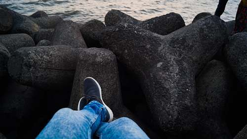 clothing person in blue denim jeans sitting infront of sea footwear