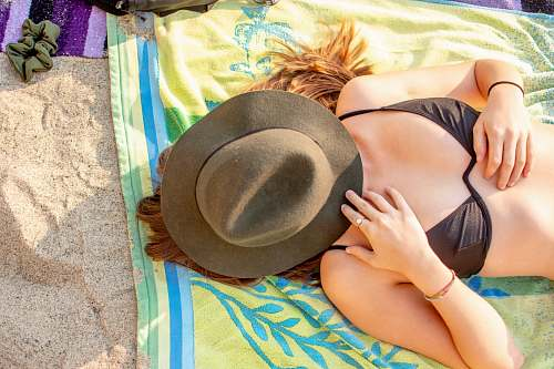 clothing woman laying down with hat covering face hat