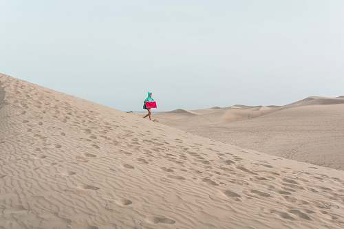 sand photo of person walking on desert holding red box soil