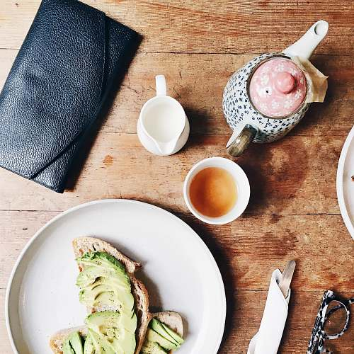 breakfast black leather long wallet beside plate avocado
