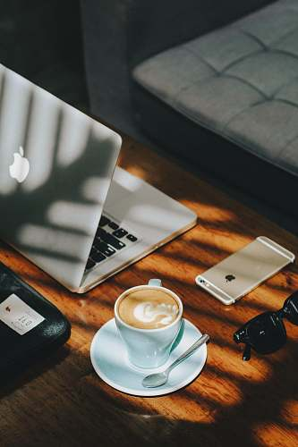 table cappuccino in white ceramic cup with saucer beside gold iPhone 6s and laptop coffee table