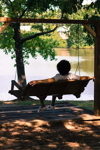 bench person sitting on hammock facing lake swing