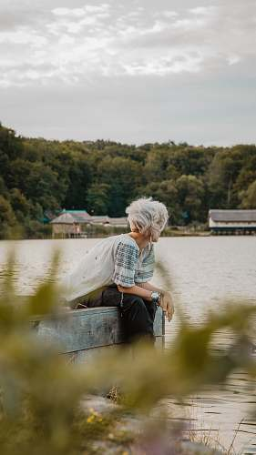 apparel man sitting on wooden dock during daytime clothing
