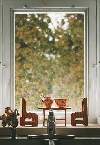 person miniature chairs and table near window window