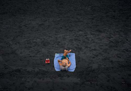 person shirtless man lying on blue picnic mat on the field sand