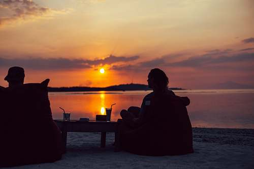 person silhouette of person sitting on chair during sunset people