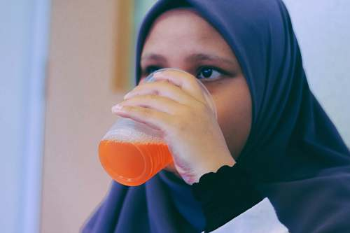 person woman in black hijab headdress white drinking people