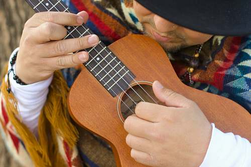 guitar person playing brown ukulele leisure activities