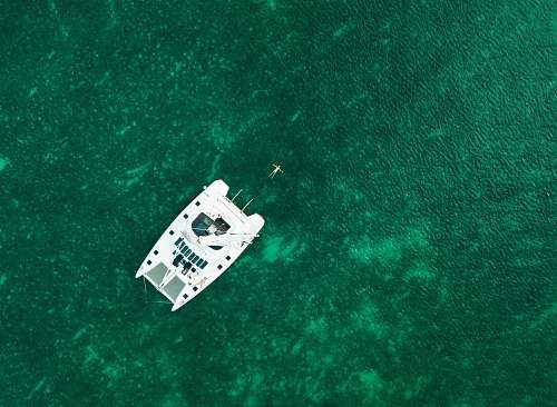 boat aerial view photography of white boat in the middle of body of water during daytime aerial view