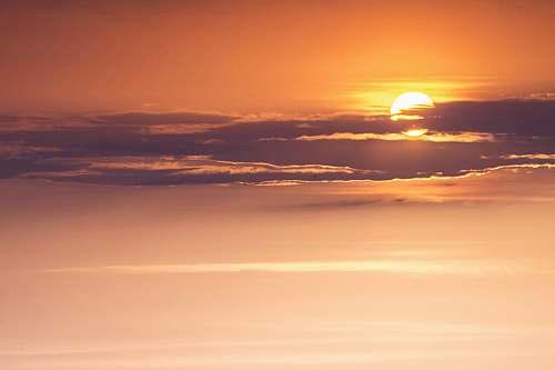outdoors orange sun behind clouds sky