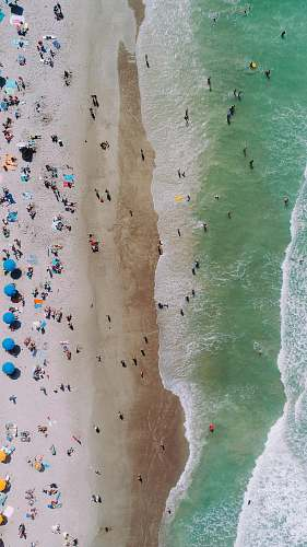 coast aerial photo of people on seashore during daytime photo beach