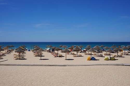 sea brown parasol on seaside during daytime beach