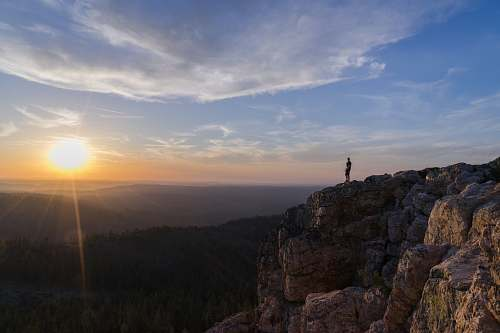 sun person standing on mountain cliff view