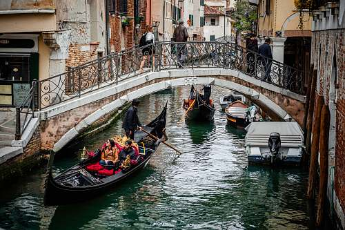 human people riding boat near bridge with people crossing during daytime gondola