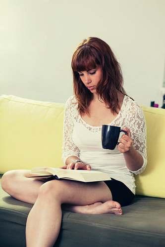 human woman wearing white lace shirt holding mug while reading book people