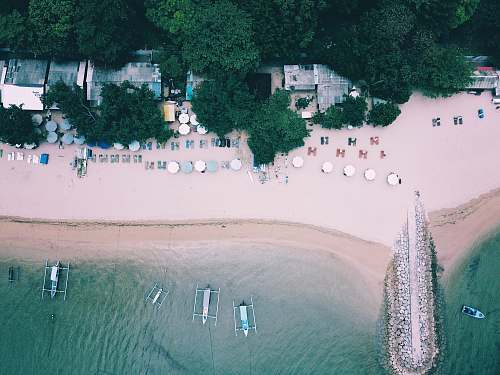 bali beach surrounded by trees and boats on ocean during daytime aerial view