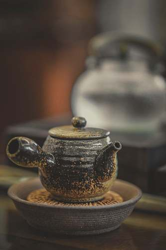 saucer close-up photography of black ceramic pot on brown surface teapot