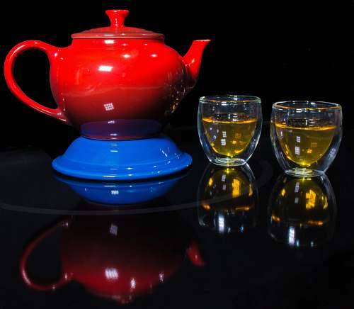 teapot red teapot on blue container beside two clear glass teacups pot