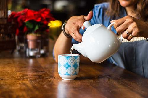 person unknown person holding white ceramic kettle cup