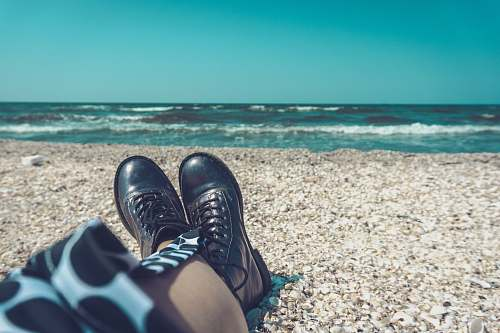 boot person wearing pair of black leather shoes sitting on seashore mamaia