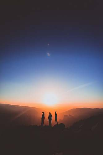 nature silhouette of three person standing on mountain outdoors
