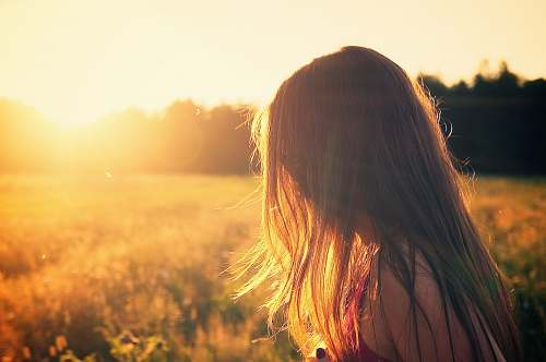 girl woman wearing black camisole top walking on grass field during sunrise woman