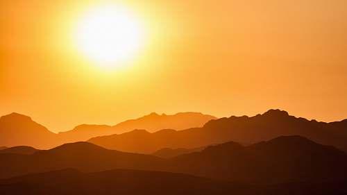 sunrise silhouette of mountains under orange sky sky