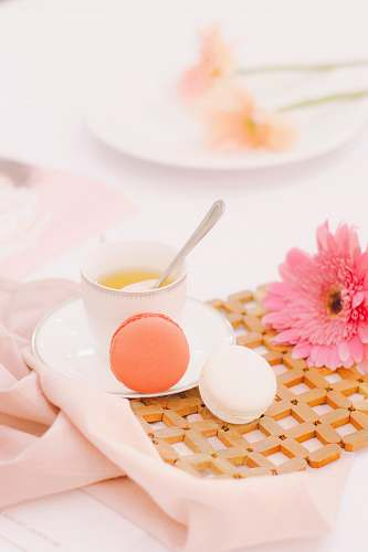 flower two orange and white macaroons beside white ceramic cup with spoon pink
