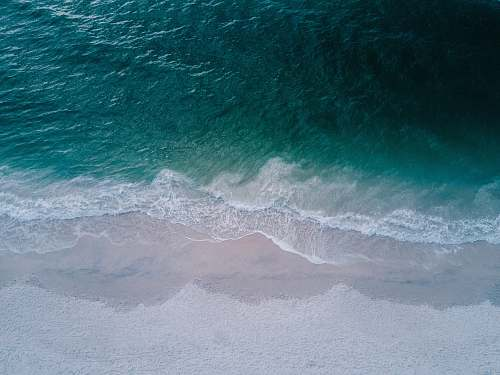ocean body of water beside sand sea