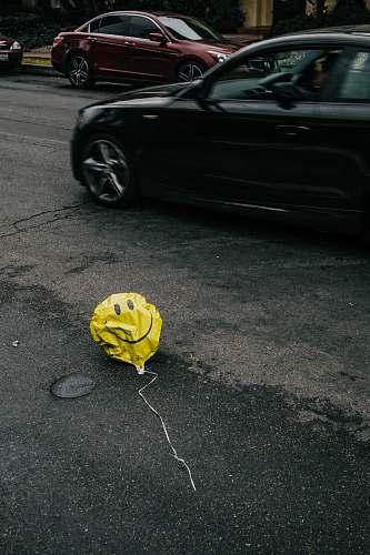 automobile smiling emoji balloon beside black car during daytime transportation