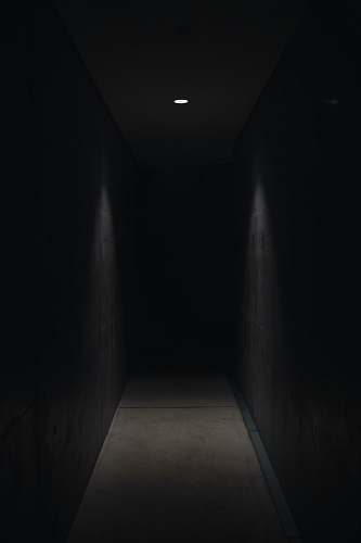 dark dark pathway lit with small light fixture horror