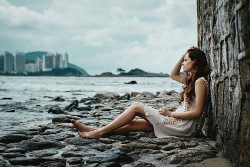 person woman leaning on stone wall near body of water human