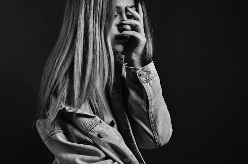 woman woman in denim jacket covering her face with her palm blonde