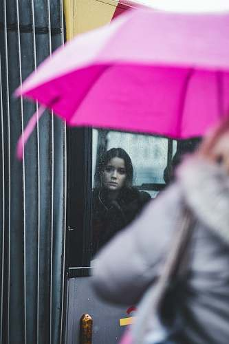 umbrella woman standing inside glass window canopy
