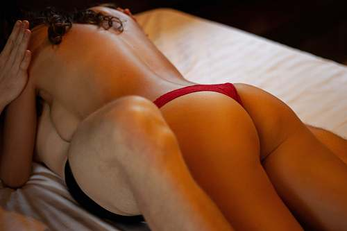 apparel woman in red panty lying on bed clothing