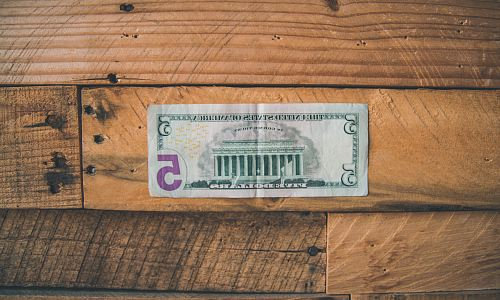 photo 5 U.S dollar on brown wooden surface free for commercial use images